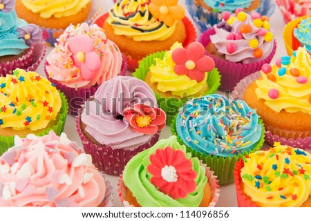 many sweet birthday cupcakes with flowers and butter cream - stock photo