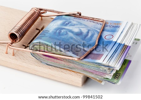 many swiss francs banknotes in mouse trap - stock photo