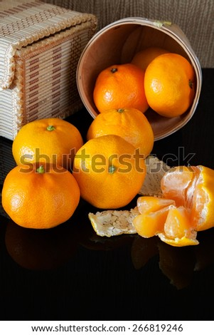 many tangerine on background wicker boxes with reflection - stock photo