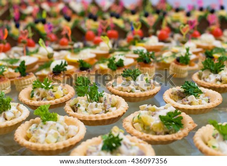 many tartlets with russian salad on buffet table - stock photo