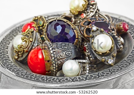 many Turkish Ottoman handmade rustic rings with pearls and corals on a silver plate - stock photo