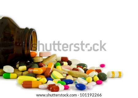 Many type of drugs pills capsules and medicine poring from the bottle with white isolation background. Medical manufacturing industry concept. - stock photo