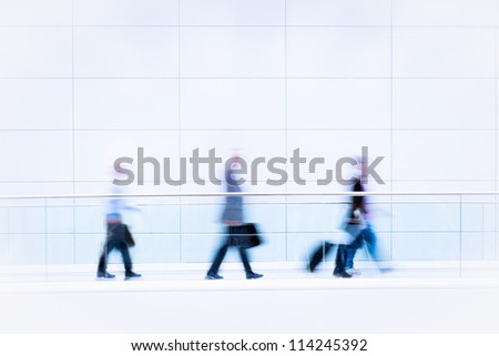 Many unrecognizable business people in front of modern architecture, intentional motion blur, blue tinted high resolution stock photo - stock photo