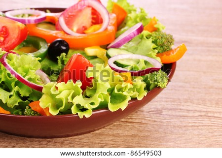 many vegetables on the plate on a wooden background - stock photo