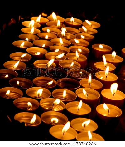 Many wax candles lit by the faithful during the celebration of the