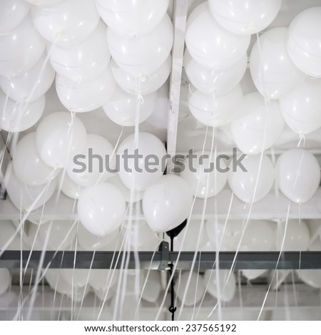 Many white balloons under the ceiling - stock photo