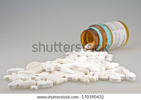 many white drugs pills shapes outside a bottle - stock photo