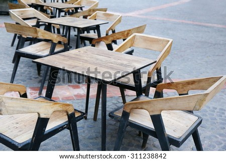 many wood table, europe cafe outdoor , ,wood tables and black chairs set up for lunch outside cafe, street side in Europe, leisure corner with wood chairs and table - stock photo