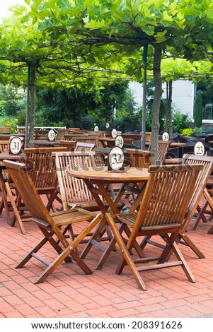 Many wooden teak tables and chairs on brick patio in cafe or restaurant - stock photo