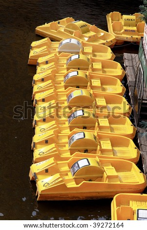 Many yellow boats for trips on a lake - stock photo