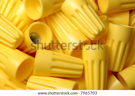 Many yellow wire nuts in a pile - stock photo