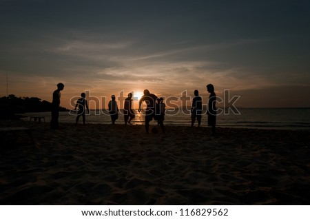 Many young people are kicking a football on the beach, the sun sets.