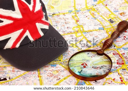Map of London, magnifier glass and cap with British flag.  Buckingham palace Close-up. - stock photo