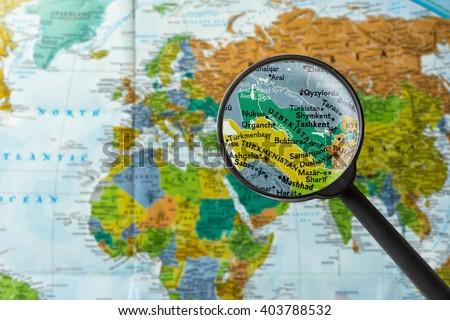 Map of Uzbekistan through magnifying glass - stock photo