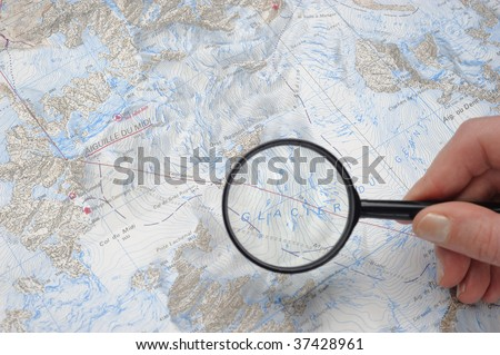 Map with  magnifying glass zooming on a glacier - stock photo