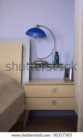 Maple headboard and a lamp with blue lampshade on a bedside table top. Blue wall behind the bed. - stock photo