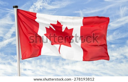 maple leaf national flag of canada against a blue cloudy sky - stock photo
