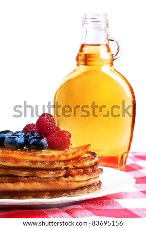 Maple syrup and pancakes with forest fruits, still life on white background. - stock photo