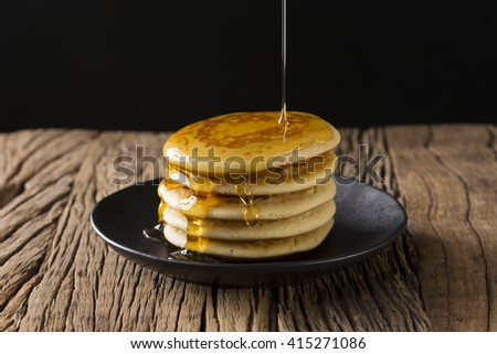 Maple syrup being poured on a stack of fresh pancakes, sitting on a rustic wooden table. - stock photo