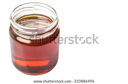 Maple syrup in a mason jar over white background
