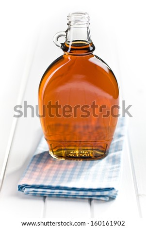 maple syrup in glass bottle on white wooden table - stock photo