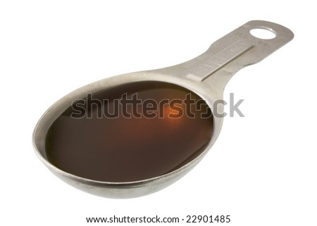 maple syrup on measuring, aluminum spoon isolated with clipping path - stock photo