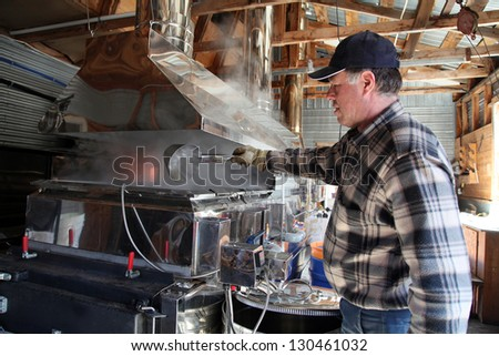 Maple syrup producer checking the thickness of the maple syrup - stock photo
