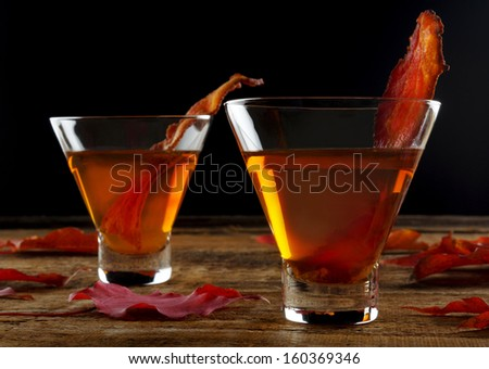 Maple whiskey bacon cocktail  on rough wood - stock photo