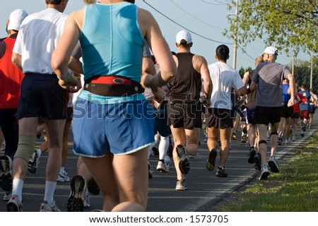 Marathon runners form a tight tight pack immediately after the start of the race. - stock photo