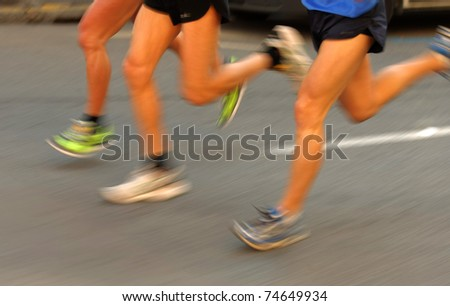 Marathon runners legs on the road followed by another runner with panning blur - stock photo