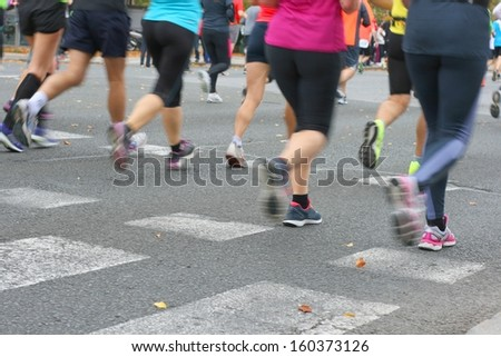 Marathon runners pictured from behind, blurred motion