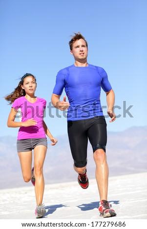 Marathon running athletes couple training in desert. Fitness sport runners living active lifestyle. Fit sports couple, Asian woman, Caucasian man. - stock photo