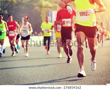 Marathon running race,male runner checking the time from his sports watch - stock photo