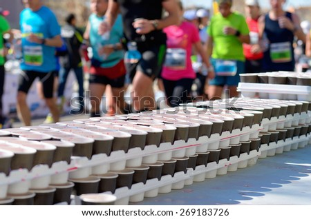 Marathon running race, runners on road, volunteer giving water and isotonic drinks on refreshment point  - stock photo