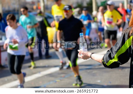 Marathon running race, runners on road, volunteer giving water on refreshment point  - stock photo