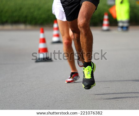 Marathoner runs very fast for the paved road in the final sprint to the finish line first - stock photo