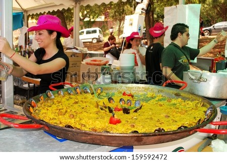 MARBELLA, SPAIN - JUNE 12, 2008 - Large paella on a cafe counter at the Romeria San Bernabe Religious Festival and unidentified bar staff, Marbella, Spain on June 12, 2008. - stock photo