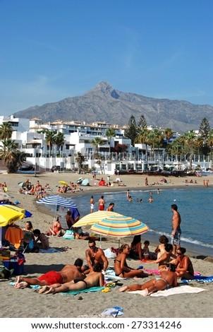MARBELLA, SPAIN - SEPTEMBER 14, 2009 - Holidaymakers relaxing on Playa de Nueva beach, Puerto Banus, Marbella, Costa del Sol, Malaga Province, Andalusia, Spain, Western Europe, September 14, 2009. - stock photo