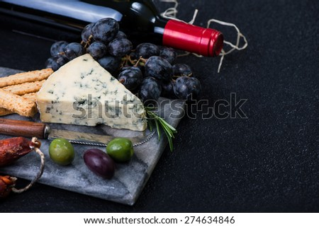 Marble board with cheese selection, wine and grapes on dark background from above - stock photo