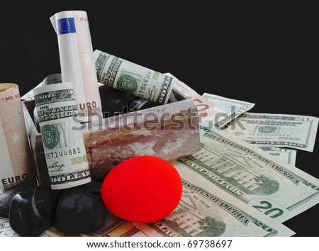 Marble box with euro and dollar currency and a reddened nest egg on the rocks depict troubled European and American pension funding, a state, national, and global finance issue