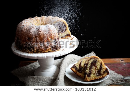 Marble bundt cake on wooden table, black background - stock photo