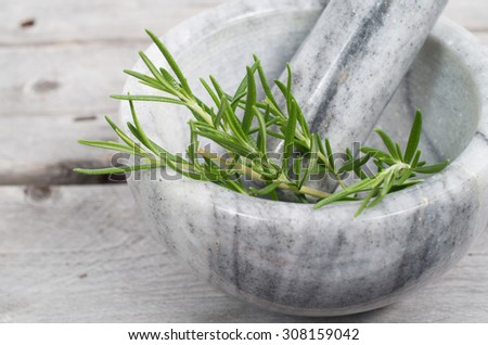 marble mortar and pestle with fresh rosemary herb sprigs on a wooden table - stock photo
