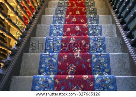 Marble stairs covered with carpet in mansion.