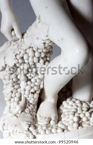 Marble statue of wine maker with grape and legs - stock photo