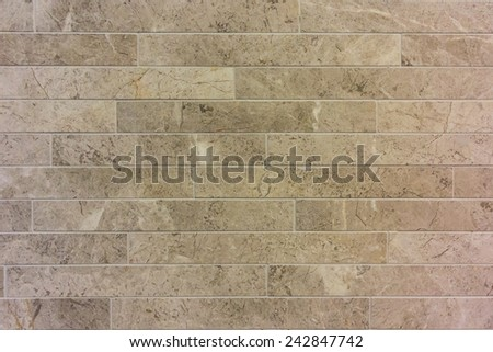 Marbled tan rectangle tiles mounted on a wall - stock photo