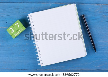 March 27, Cube calendar and notebook on wooden surface with copy space - stock photo