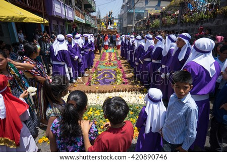 March 25,2016 San Pedro la Laguna, Guatemala: people in traditional costumes lined up along the street covered with colorful saw dust and flowers during Easter procession