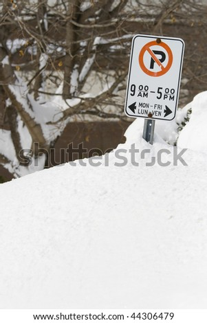 MARCH 9 2008: Snow drifts as high as the street side parking signs after a heavy snow storm in Ottawa Ontario Canada. - stock photo