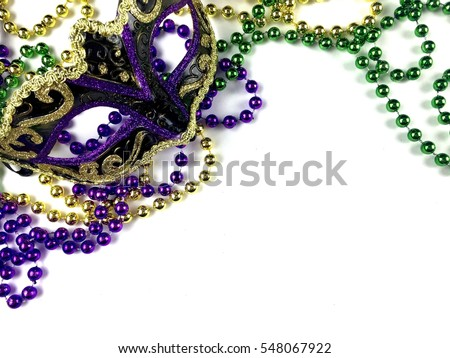 Mardi Gras beads and mask on a white surface