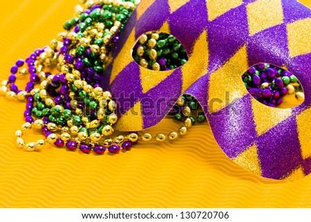 Mardi Gras beads and mask on yellow backgound. - stock photo